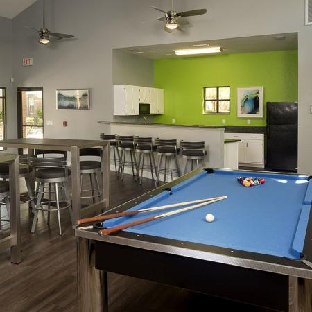 Community clubhouse with pool table, hightop table and chairs, bar seating with cabinets and appliances in background.
