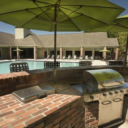 Outdoor grill encased in brick bar with bar stools on opposite side.  Sun umbrellas, pool and leasing office in background.