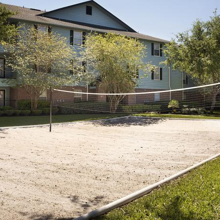 Sand volleyball court with buildings and trees in background.