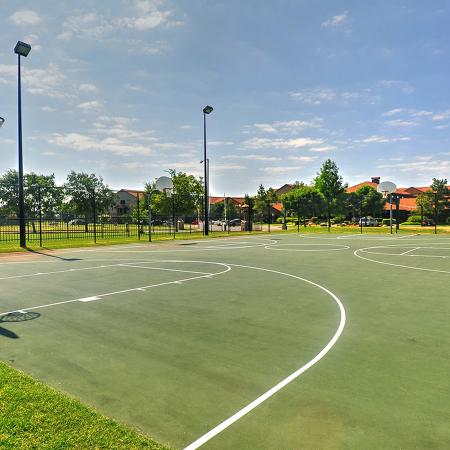 Full size basket ball court with buildings and trees in background.