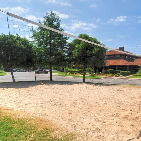 Beach volleyball pit surrounded by green grass, trees and apartment building in background.