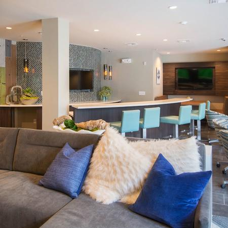 Community clubhouse with sectional couch, pillows, bar with bar stools, wall mounted televisions on back wall.