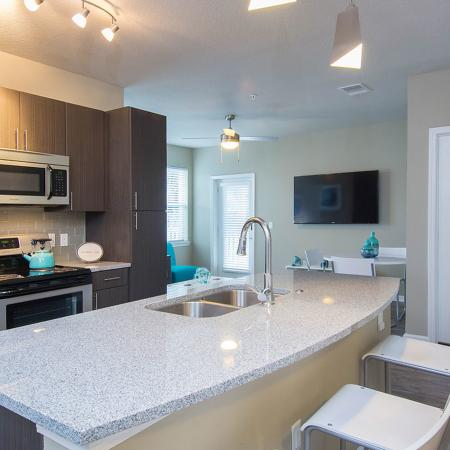 Kitchen area with wood tiled floors, stainless steel appliances, dark cabinets, modern lighting.