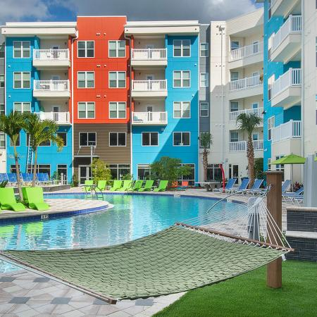Community pool area with hammock in foreground, green lounge chairs and residential buildings in the background.