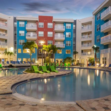 Dusk photo of community pool surrounded by multi-colored pavers, colorful lounge chairs, palm trees, and four floors of balconies on each side.