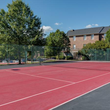 Red colored tennis court with trees and building in background.