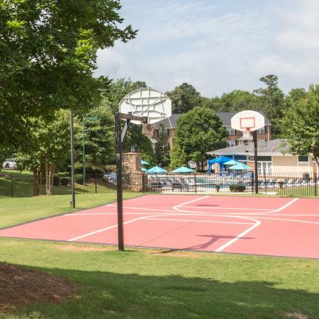 Full size basketball court surrounded by grass, pool in background.