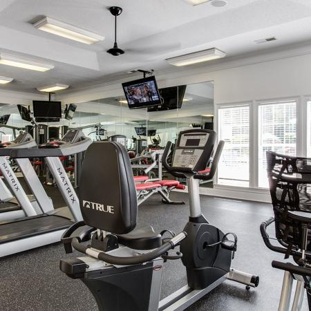 Community fitness center with various exercise equipment and ceiling mounted televisions.