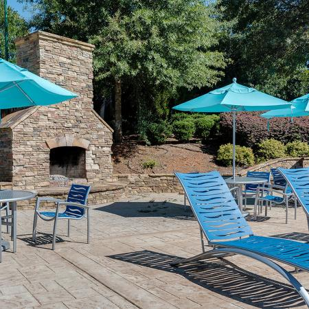 Lounge chairs outdoor tables with sun umbrellas, and stone fireplace in background.