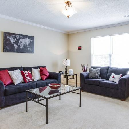 Carpeted living room with couch, love seat, glass coffee table and ceiling fan.