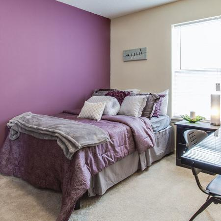 Bedroom with purple colored wall and purple bedspread. Glass desk and chair in foreground.