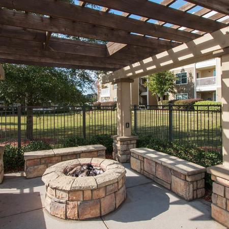 Stone fire pit underneath wood framed gazebo.