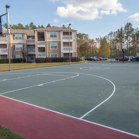 Full size basketball court with apartment buildings in background.