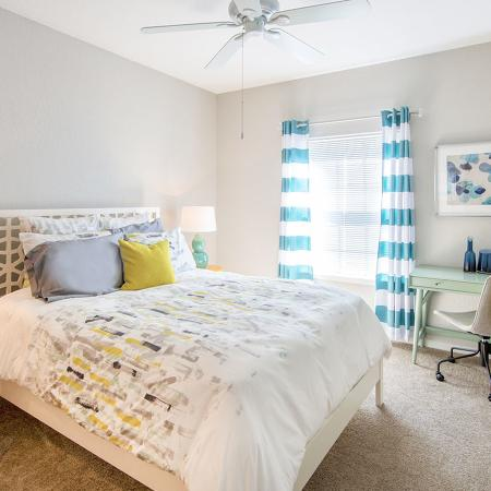 Bedroom with bed, nightstand, desk and chair.