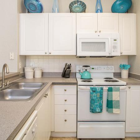 Kitchen with double sink, white cabinets and white appliances.