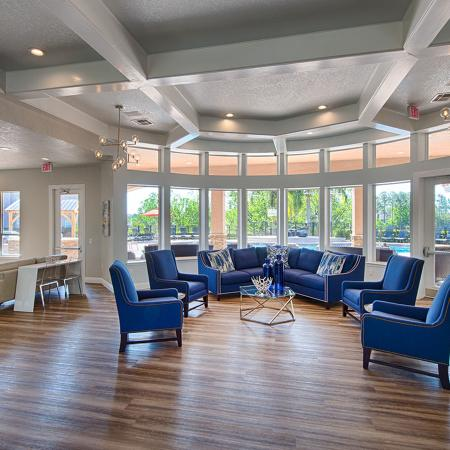 Large room with blue couch and blue chairs.  Large windows overlooking the pool,