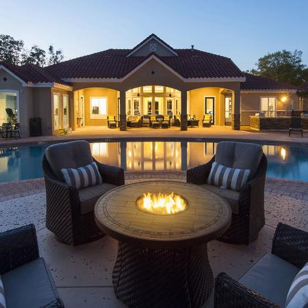 Fire table with chairs.  Pool and lighted porch in background.