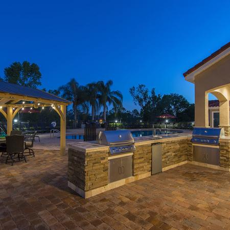 Outdoor kitchen with grills, table gazebo.