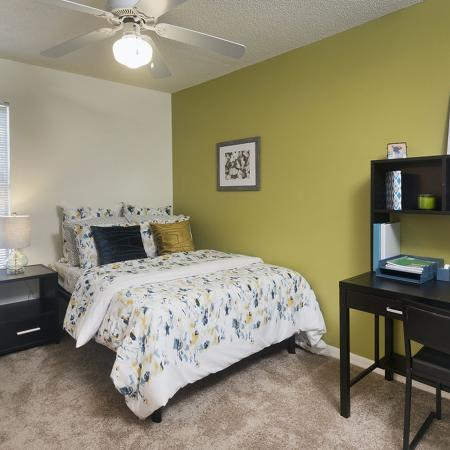 Bedroom with window, green accent wall, ceiling fan, carpet, end table, study desk and drawer.