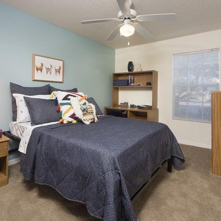 Bedroom with window, teal accent wall, end table, bed, ceiling fan, study desk and drawers.