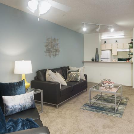 Carpeted living room with teal accent wall, ceiling fan, 2 couches, end table, coffee table, and pass through to kitchen.