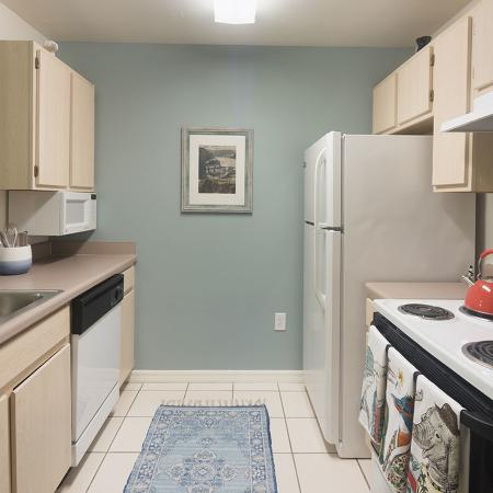 Kitchen with dishwasher, stove, fridge, microwave, tile floors, and cabinets.