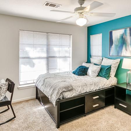 Carpeted bedroom with blue accent wall.  Bed has a gray patterned bedspread and a set of dark dresser, desk with chair and nightstand.