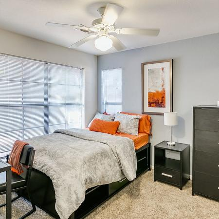 Carpeted bedroom with light blue accent wall.  Photo shows a set of dark dresser, nightstand, and desk with chair.  Bed has a gray bedspread and pillows.