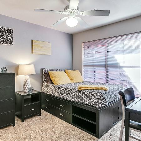 Carpeted bedroom with blue accent wall.  There is also a dresser, nightstand, desk with chair, and all dark wood.