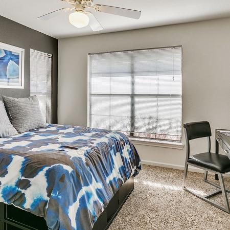 Bedroom with brown carpet, blue and brown bedspread, desk with chair and paintings on dark accent wall.