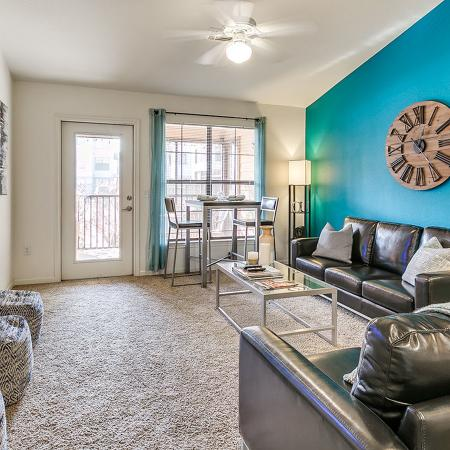 Carpeted living area with blue accent wall, leather couches, glass coffee table and wall mounted television.  Front door and window on the back wall.