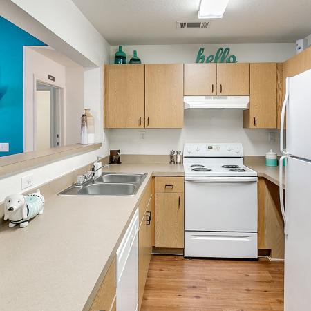 Galley style kitchen with wood style flooring, white appliances, double sink.