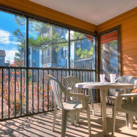 Screened patio with small table and four chairs.