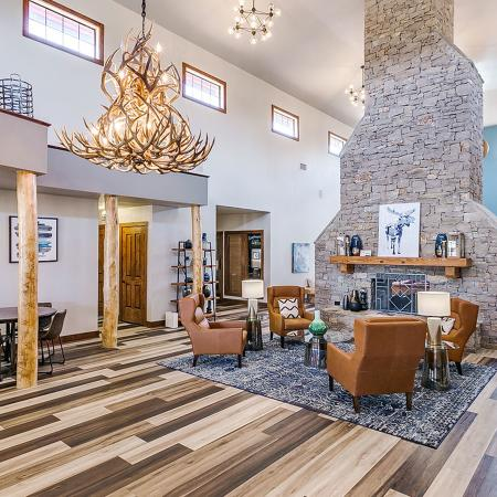 Community social center with wood style flooring, large, leatherback chairs in front of a large stone fireplace with chimney extending up to the tall ceiling.