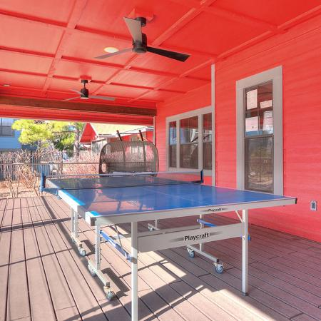 Covered, outdoor game area showing pink pong table under two ceiling fans.