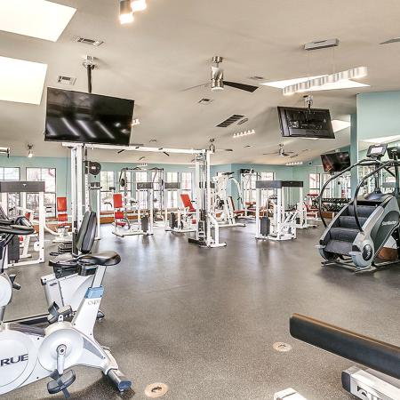 Community fitness center with various cardio and weight machines.  Several televisions hanging from ceiling.
