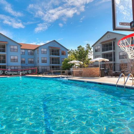 Another community pool photo showing a basketball hoop, hanging over the water, lounge chairs, and water volleyball net in the distance.  Apartment buildings and blue sky fill the background.