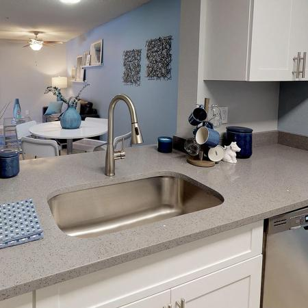 Under-mounted sink with modern faucet, looking into dining area.