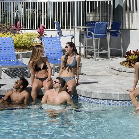 Community pool shot with seven young people in bathing suites, talking.