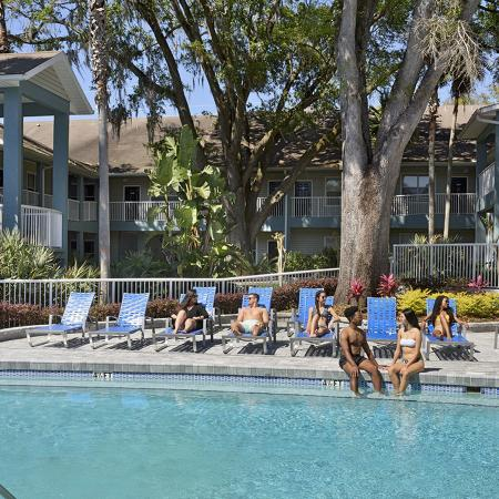Community pool lined with lounge chairs and people sitting in them.  Trees, buildings, and pool fence in background.