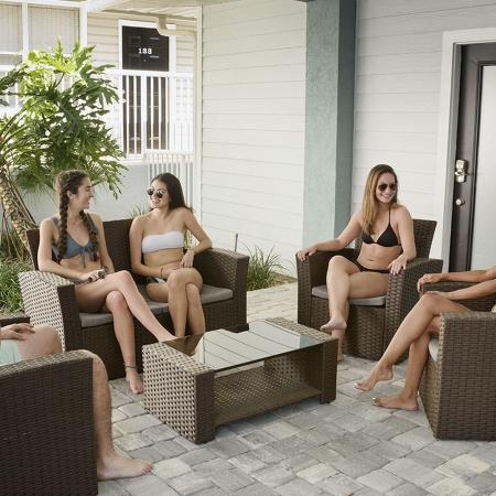 Several young adults sitting on outdoor furniture talking.