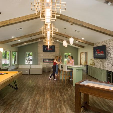 Wide angle shot of community clubhouse with sitting area, billiards, shuffleboard, and kitchen area.