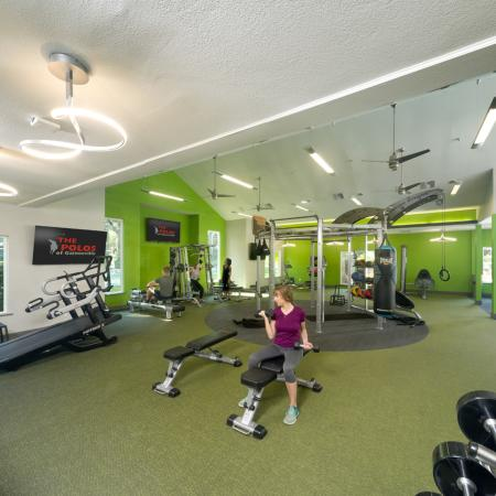 Wide angle of fitness center with free weights and cardio area in the background.