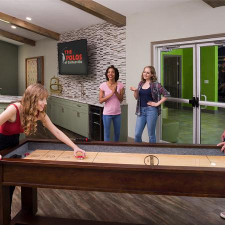 Residents playing shuffleboard inside the upgraded community clubhouse.