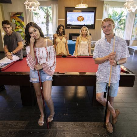 Five young people posing around a pool table in Seminole Grand's community clubhouse.