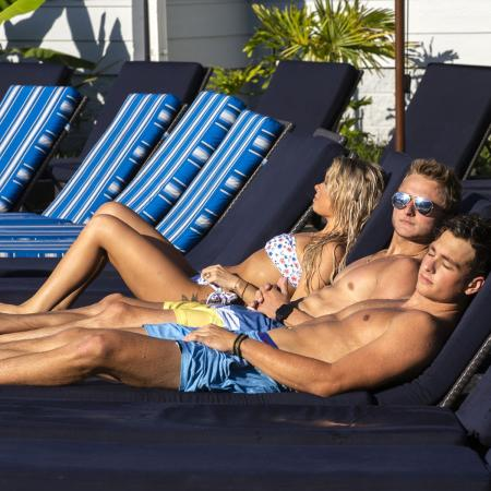 Three young adults laying on lounge chairs, poolside.