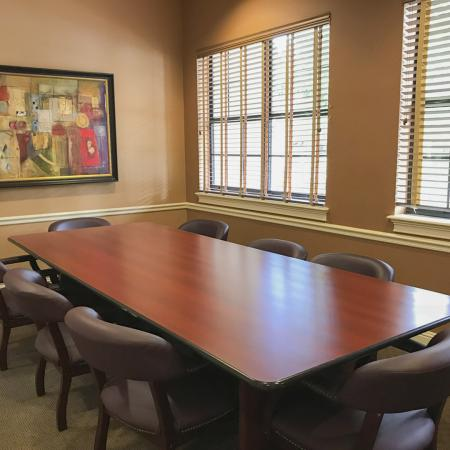Community meeting room with large, rectangular table, eight chairs, windows with blinds open and painting on far wall.