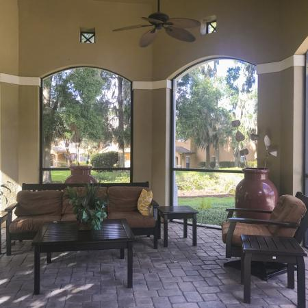 Community screened in patio with outdoor couch, chair and tables under a ceiling fan.