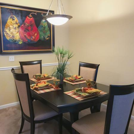 Carpeted dining area with wood dining table and four place settings.  Painting of pears in background.