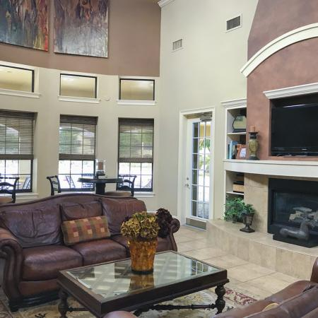 Community clubhouse with tall ceiling, leather couches, glass coffee table, and fireplace.